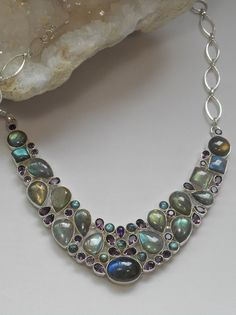 A one-of-a-kind hand polished cabachon Labradorite necklace with 17 highly chatoyant and richly-hued Labradorite gemstones, adorned with 33 sparkling faceted Amethyst gemstones, set in 925-hallmarked