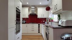 Wren Edwardian Cream kitchen with red glass splashback, ivory metro tiles, nutmeg engineered wood floor and Unsui Silestone work surfaces