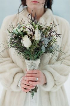 winter wedding bouquet with white roses & evergreens eucalyptus, hand-tied with cream yarn and detail of broach