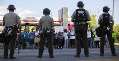 Ferguson police officers stand off with protestors of the shooting