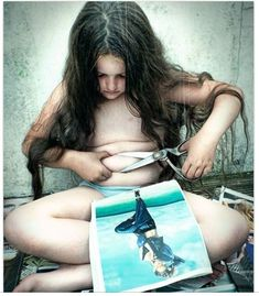 Due to society common stereotypes, little girls are trying alter themselves to look like people in the media. In this photo a little girl is making an attempt to cut off the fat off of her stomach to look like the image of the woman in her lap. If children were taught self-love from a young age they would, find ways to love their selves as they are.