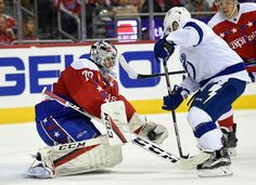 Washington Capitals goalie Braden Holtby (70) stops the puck against Tampa Bay Lightning center Tyler Johnson, right, during the second period of an NHL hockey game, Friday, Dec. 23, 2016, in Washington. (AP Photo/Nick Wass)
