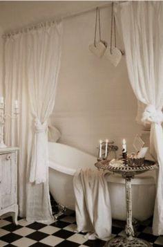La bonne façon de mettre en valeur unr jolie baignoire sans etre isolée au milieu d'une grande piece froide. Et le joli guéridon a coté est parfait! Penser a planquer les etageres de rangement derriere les rideaux