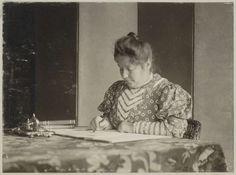 Anonymous | Vrouw schrijvend aan een tafel, Anonymous, c. 1900 - c. 1910 | Onderdeel van Familiealbum met onder meer foto's van Wijnhandel Kraaij & Co. Bordeaux-Amsterdam.