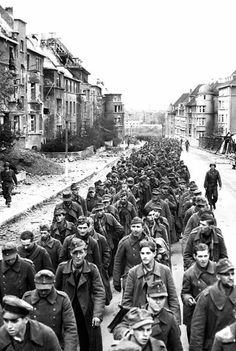"""The endless procession of German prisoners captured with the fall of Aachen marching through the ruined city streets to captivity."" 10/1944."