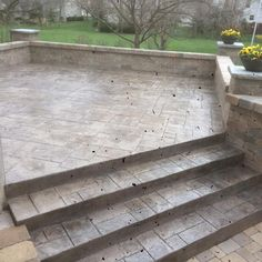 Raised stamped concrete patio with walls and lower paver patio.