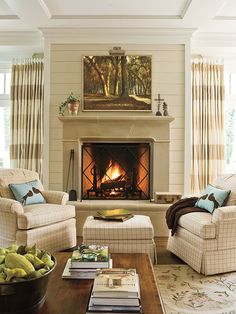 This neutral living room is serene and calm without being boring. Details in sky blue and light green, like a pair of accent pillows, a large landscape painting, and potted ivy, spruce up this cozy fireplace. (Photo: Erica Georges Dines)