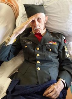 Justus Belfield, 98, salutes in photo taken by center staff on Tuesday. He passed away Wednesday. He spent his last full day on earth in his army uniform, lying in bed at Baptist Health Nursing and Rehabilitation Center in Scotia with his wife Lillian in her own bed next to him.