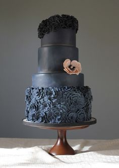 Stella - Gorgeous black ombre four-tier cake with a lovely peach flower accent. We love the ruffled bottom tier, offset by the ruffled wreath topper.