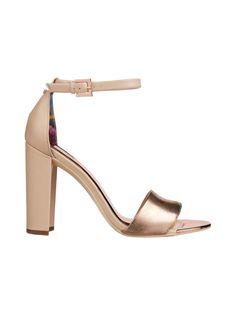 Näyttävissä sandaaleissa on paksu tolppakorko, metallinhohtoinen remmi ja pieni rusettisomiste kannassa. Nilkan ympärillä on soljellinen remmi. Koron korkeus takaa on 10 cm. Sandaalit viimeistelevät juhlatyylin! <br/><br/> UK-koot.