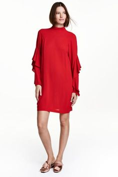 Knee-length dress in viscose crêpe with a small stand-up collar, opening with covered buttons at the back of the neck and long raglan sleeves with flounces.