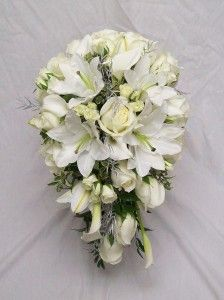 White roses and lilies in very traditional teardrop bouquet.