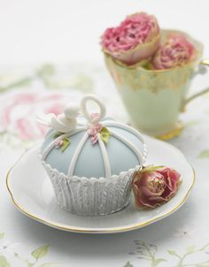 A birdcage cupcake, with piped blue and white frosting and a tiny bird decoration. Cupcake by Zoe Clark of The Cake Parlour.