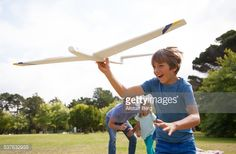 Boy, aged 9, playing with a toy plane, watched by his family in a park