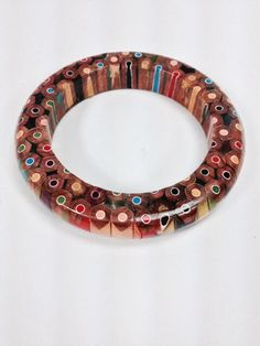 This is a lathe turned bangle bracelet made from Colored Pencils. This is so cute I cant contain myself. This is a perfect gift for the student, artist, teacher or someone who loves color in their life. It is coated with a high gloss protective finish.  The inside diameter is 2 1/2 inches and the outside diameter is 3 1/2 inches. Determine your size by measuring a solid round bracelet you are comfortable wearing or make a paperboard sleeve that slides over your hand without flexing and…