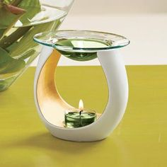 """Embrace Fragrance Warmer Modern sculptured white resin holder with rich golden interior creates a feel of luxury. Heat from a tealight releases the fragrance of Scent Plus® Melts placed in the glass dish. Melts and tealight sold separately. 4¾""""h."""