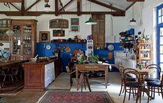O estilo rústico predomina nesta cozinha, que, apesar da madeira escura, é bem iluminada pelos janelões do galpão que foi transformado em casa pelo antiquarista Paulo Ribeiro Pereira. Um balcão de farmácia separa o ambiente da sala de jantar