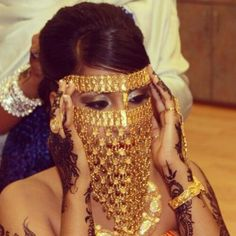 Somali bride in gold headdress and traditional henna getting ready