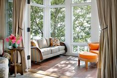 Michigan Lake House sun porch with pops of orange color.  Curtains can close off the area when needed.