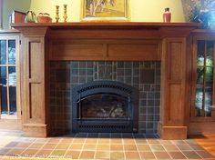 An elaborate Arts and Crafts fireplace surround, with built-in bookshelves on both sides of the fireplace. A classic Craftsman arrangement.
