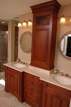 A storage cabinet tower includes a glass inset for display, crown molding and separates dual vanities in this his & her bathroom by Neal's Design Remodel.