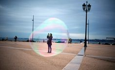 A tourist is seen through a soap bubble as she takes a picture at Comercio square in downtown Lisbon, Portugal November
