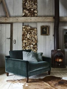 A sleek, mid-century modern armchair (this one's by Barker and Stonehouse) carves out a contemporary corner in this otherwise rustic room, especially when upholstered in this season's trendiest material: velvet.