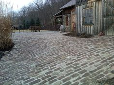 Old English Cobblestones.  Mellow tones of plum, brown and tan are reminiscent of a picturesque village in the Cotswolds...but this uniquely beautiful Medina sandstone was actually quarried here in America. It was a popular choice for buildings and towns in western New York and eastern Ohio dating back to the early 1800s. Belgian Block, Cobblestone Driveway, Driveway Landscaping, Driveway Pavers, Driveway Ideas, Recycled Brick, Front Walkway, Concrete Pavers, Brick And Stone