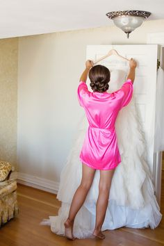 Picture of the bride about to put on her dress