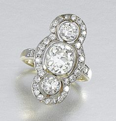 DIAMOND RING, EARLY 19TH CENTURY.  Centring on a millegrain-set oval-shaped diamond flanked by two circular-cut stones to a similarly-set open work scalloped surround,