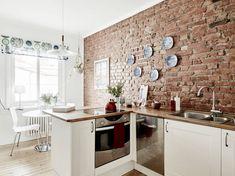 Skandynawska kuchnia z białymi szafkami z drewnianymi blatami i ścianą z czerwonej cegły
