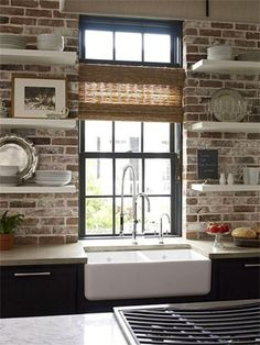 Modern style meets old-world charm... exposed brick kitchen backsplash with open shelving over apron sink and gray cabinets. White grout in brick wall for more contrast