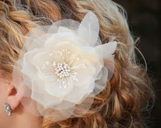 This gorgeous pure silk rose with stamen center is made in the old European style, high quality, hand made craftsmanship. The flower is perfectly accented with a single biot feather curl, rooster hackle feathers, silk leaves, and a hint of Russian netting. It is attached to a silver alligator clip for a secure hold in any hair style. This stunning hair piece measures approximately 6 x 5 inches including the feathers and leaves. The flower itself measures approximately 4 inches in diameter…