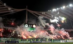 Panathinaikos fans hold flares before a Greek Super League match. The game was abandoned with eight minutes to go because of escalating clashes between fans and the police.