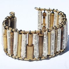 """Handrolled paper beads made from a vintage French book on French history titled """"Histoire de France,"""" hand coiled bronze guitar string beads, sections of brass tubing and a variety of brass objects from vintage clocks. The beads are on annealed steel wire strung on to silver toned copper wire with hand coiled brass wire spacer beads in between each bead."""
