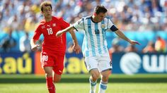 Lionel Messi of Argentina controls the ball as Admir Mehmedi of Switzerland gives chase.