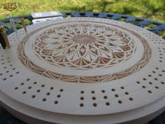 16-pointed rosette design with swirl rosette center chip carved in 11'' basswood cribbage board. The piece is finished with light brown g...