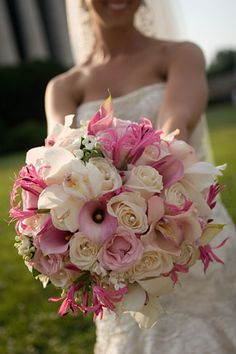 Pink and ivory round bouquet of roses, callas, orchids, and nerines.