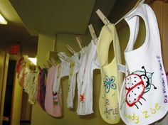 decorate plain bibs with fabric paint, stamps, and maybe iron on things?