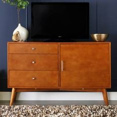 Walker Edison& angelo:HOME Mid-Century TV Stand is modern yet elegant, with plenty of storage. It fits flat panel TVs up to and features 3 drawers, a side cabinet with adjustable shelves, and a cable management system.