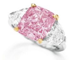 The Vivid Pink by Graff. Set with a cushion-shaped fancy vivid pink diamond weighing 5.00 carats, flanked on either side by a shield-shaped diamond, mounted in platinum and 18k rose gold.