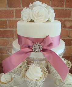 Make my own cheap cupcakes with these beautiful liners and have a top cake with fondant made for cutting (use pretty ribbon and own brooch, put silk flowers on top) --- Very affordable but still elegant!