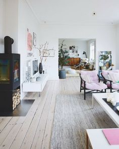 living room with neutral colors, a touch of pink and different kinds of woods.