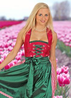 Fesches und apartes MondKini Dirndl in herrlich aufeinander abgestimmten Farben !  Nicht nur auf dem Oktoberfest stehen Sie mit diesem tollen Dirndl im Mittelpunkt.  Das pinkfarbene Oberteil begeistert duch die feinen aufgestickten Blumen. Sehr reizend sind die Miederhaken in Blumenform. Schürze, Satinschnürung und die Borte am Ausschnitt in herrlichem tannengrün runden das Kleid harmonisch ab. Zu finden aus www.trachtenmode-dirndl-lederhosen.de