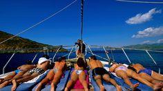 Sunbathers on bow deck of boat on Fethiye bay