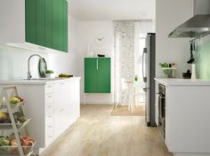A small modern kitchen with white drawers and green doors.