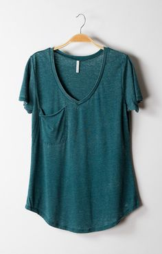 This versatile tee features a low V-neckline, a slouchy pocket and a rounded hemline. The long hemline sits at or below the hips which allows this tee to be layered with vests and sweaters or paired w