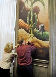 Valinda Freed, left, vice chairwoman of the Missouri Republican Party, writes on a business card atop a Thomas Hart Benton painting in the Missouri Statehouse.