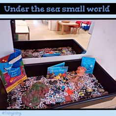 'Under the sea' sensory tray with aquatic gravel, rocks and sea creatures.