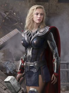 Amber Heard stands in full Thor armor and red cape, wielding a giant hammer, in front of rubble
